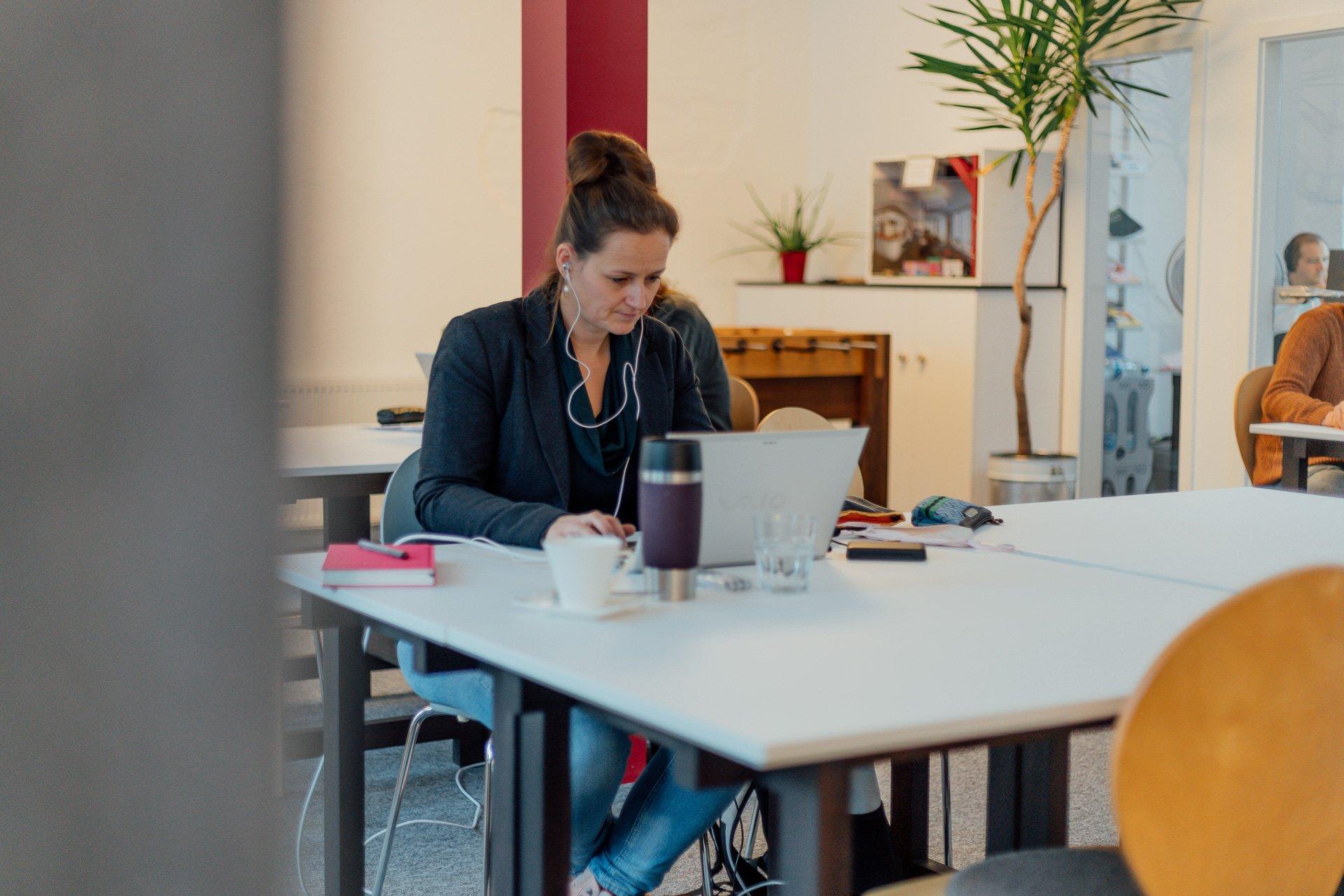 Personen arbeiten konzentriert im Flex Desk Bereich