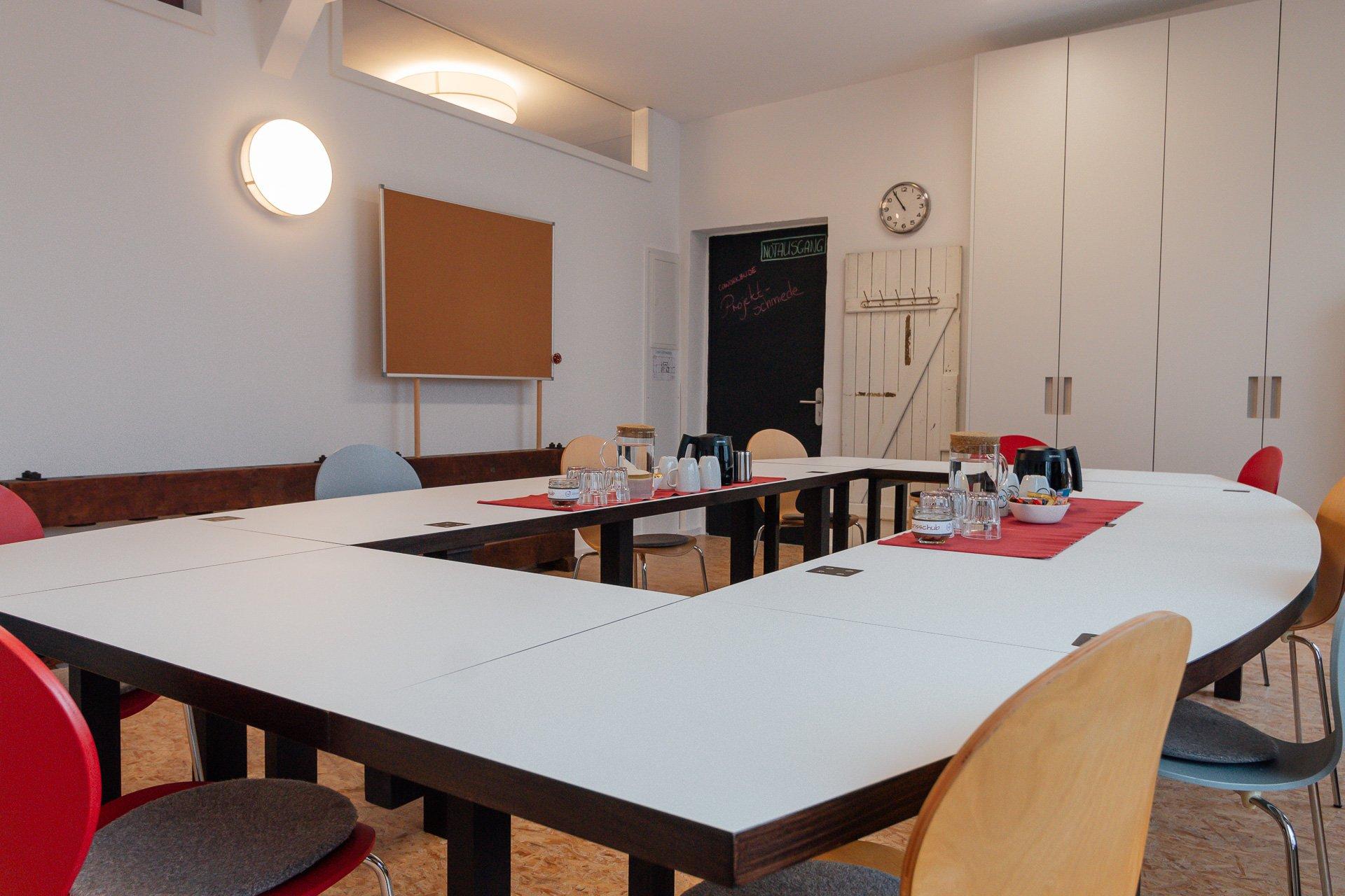 Konferenzraum mit Pinnwand vorbereitet für Teilnehmer:innen