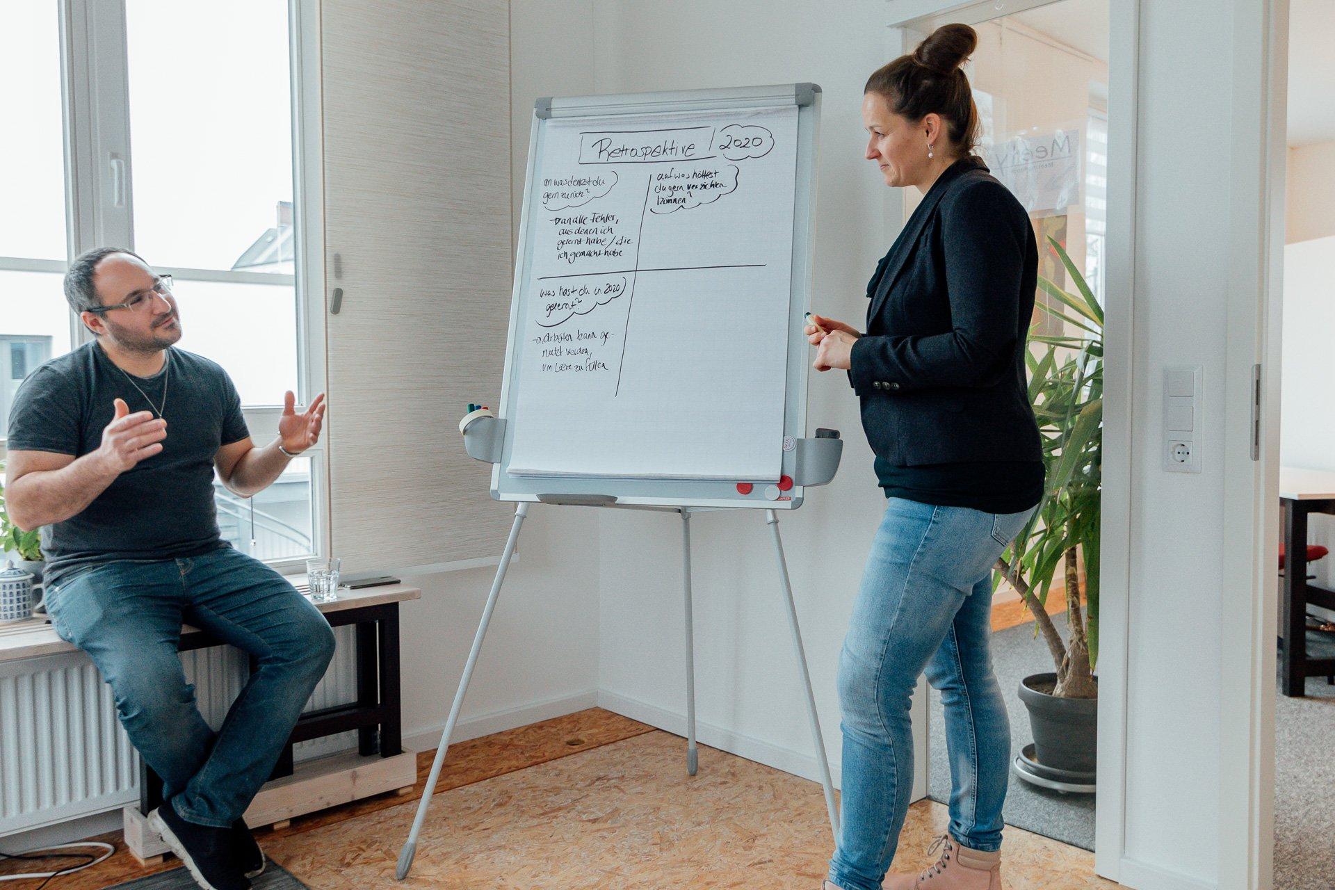 Zwei Personen bei einem Coaching mit Flipchart